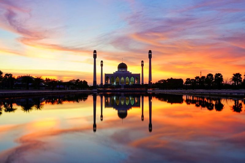 Symmetry view of mosque by lake against dramatic sky during sunset