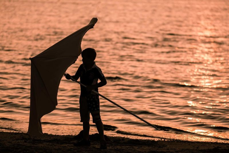Full length of boy holding parasol while standing at beach during sunset