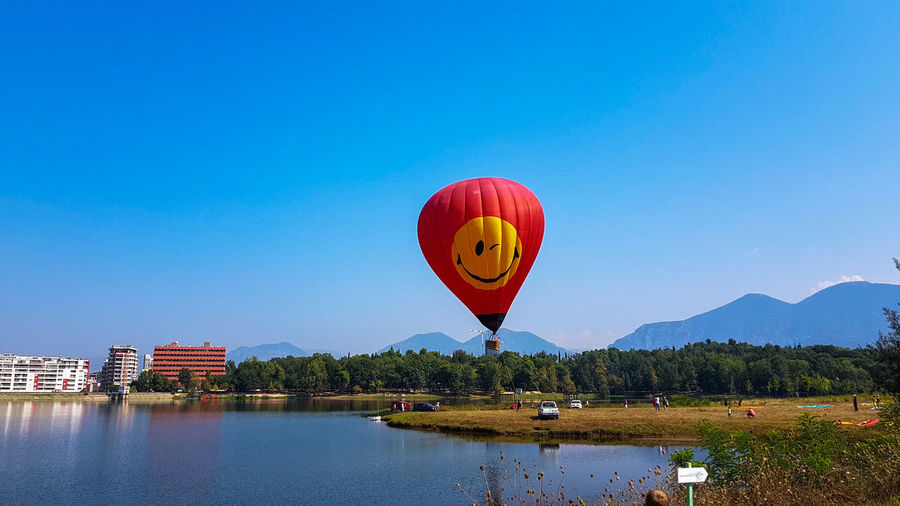 Artificial Lake Of Tirana Cityscape Photography EyeEm Selects Hot Air Balloon Water Lake Clear Sky Floating On Water Blue Sky Waterfront Ballooning Festival Boat Moored Nautical Vessel Calm Standing Water Rippled