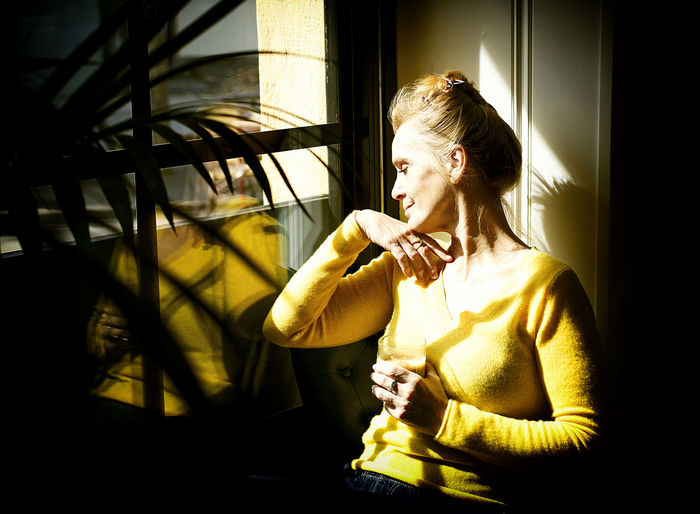 Young woman sitting by window at home
