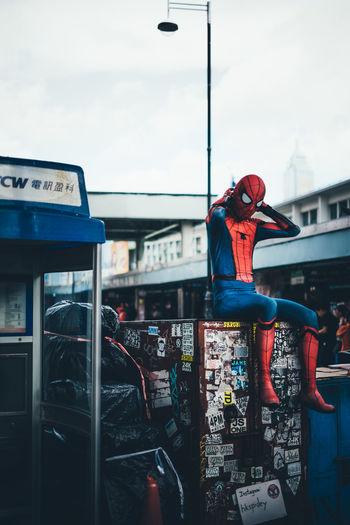 Man in bus against sky in city