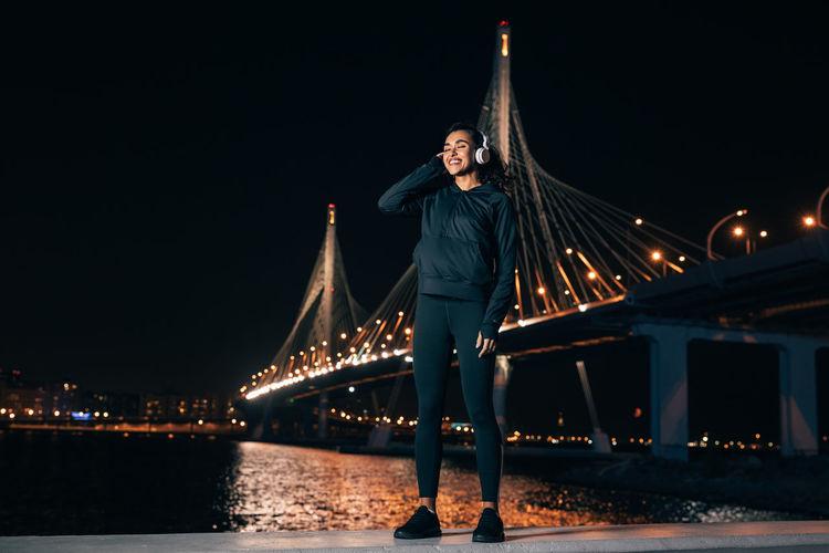Woman standing on bridge against illuminated city at night
