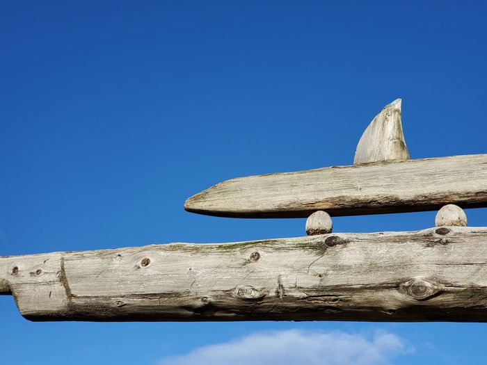 Low angle view of old wooden fence against clear blue sky