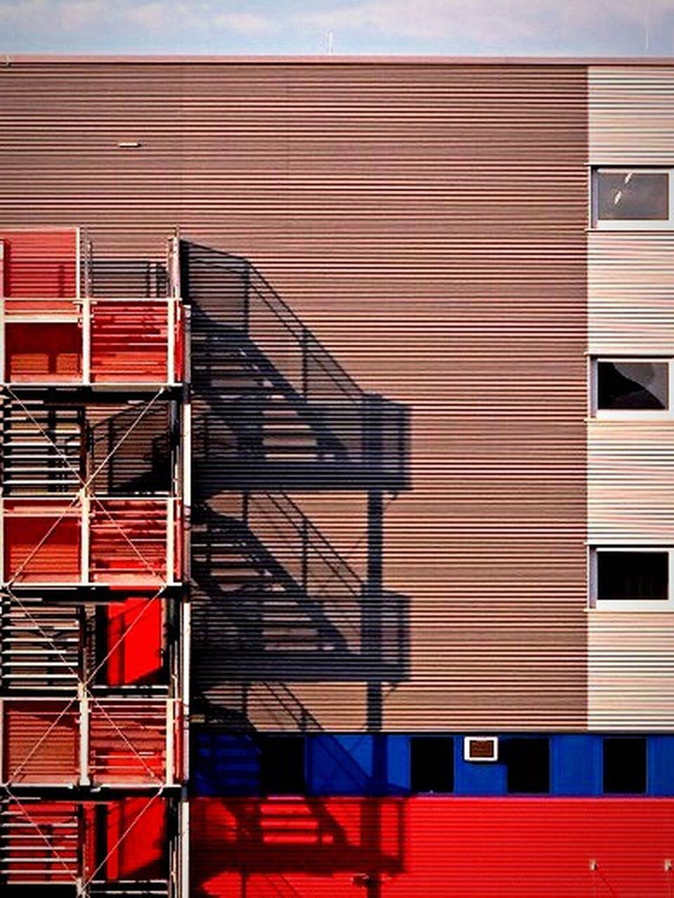architecture, red, building exterior, industry, built structure, day, no people, building, nature, outdoors, metal, cargo container, sunlight, blue, in a row, freight transportation, container, stack, shadow, transportation, iron