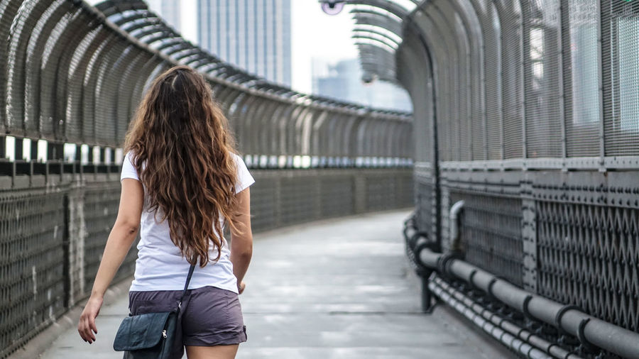 Rear view of woman walking on footbridge in city
