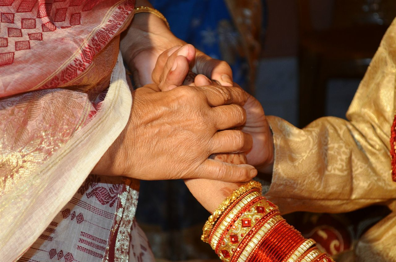 Close-up of mother holding bridegroom hands