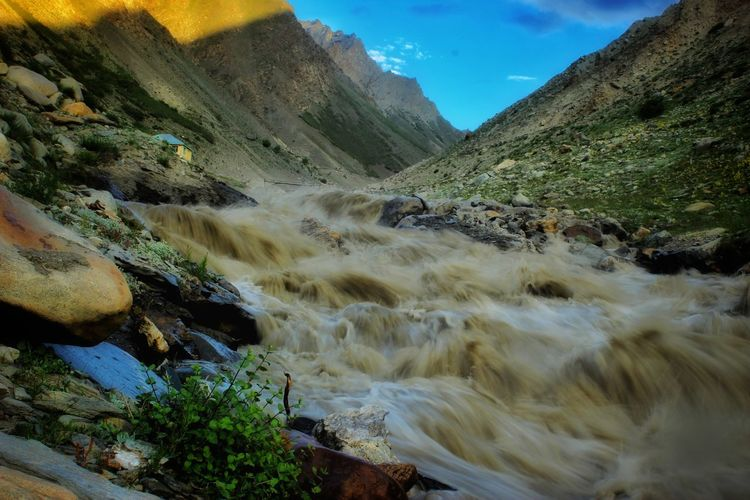 Scenic view of muddy river captured with a long exposure in a valley against sky