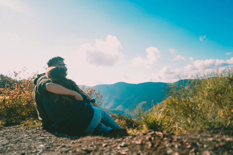 Rear view of couple sitting against mountain and sky