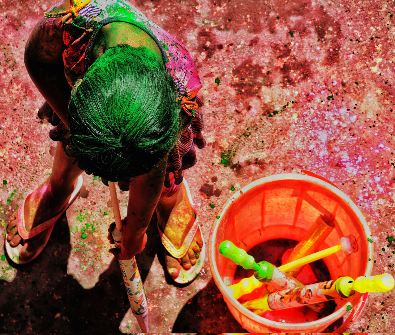 High Angle View Of Girl Playing Holi With Squirt Gun