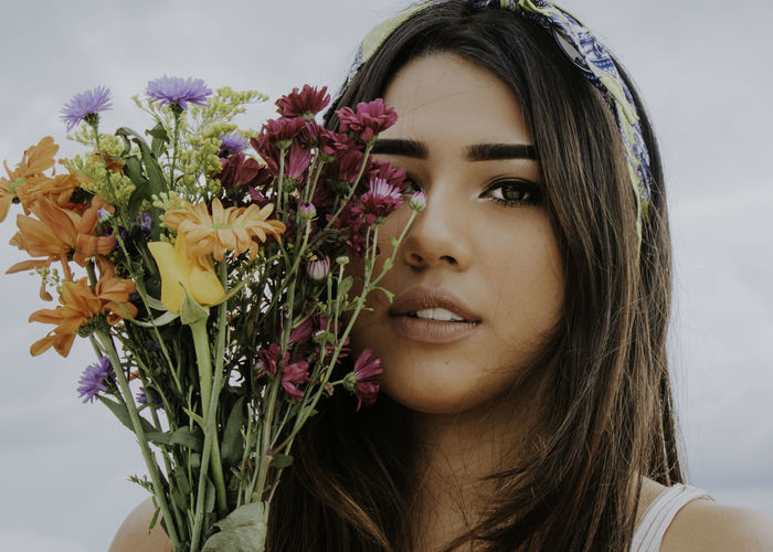 Close-up portrait of beautiful woman with bouquet