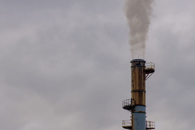 Low angle view of a smoke stack against sky