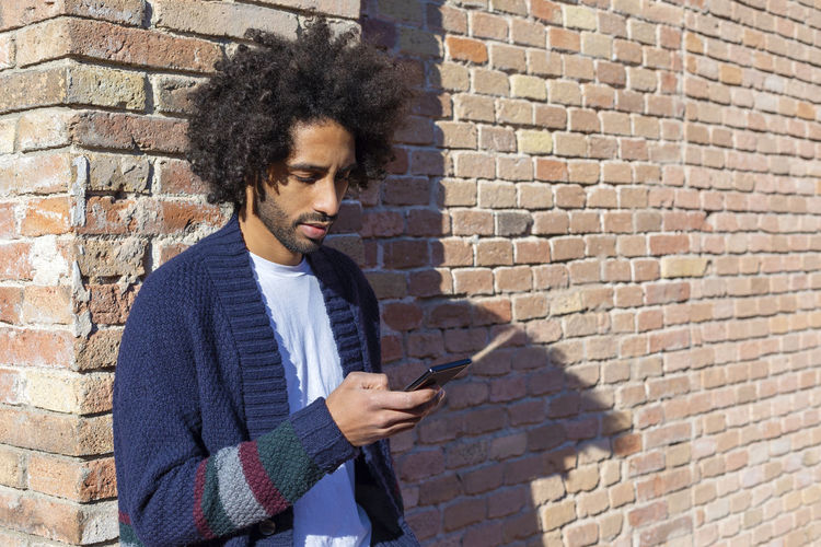 Young man using phone while standing against brick wall