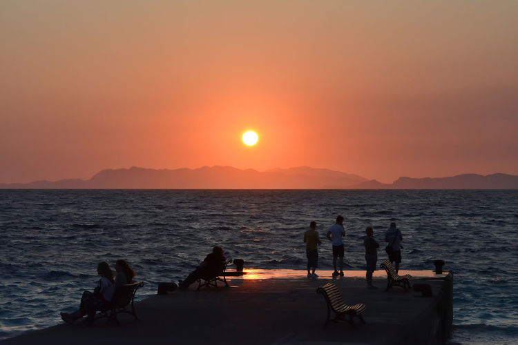 Beauty In Nature Group Of People Horizon Horizon Over Water Idyllic Land Nature Orange Color Outdoors Real People Relaxing Moments Scenics - Nature Sea Silhouette Sky Sun Sunset Water