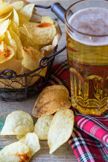 High angle view of fresh potato chips in metal basket by beers on table
