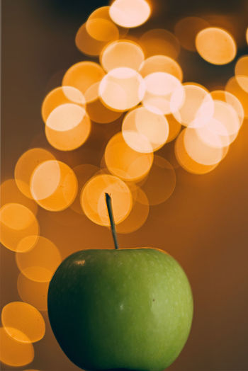 Green Granny Smith Apple Food And Drink Fruit Healthy Eating Food Apple - Fruit Close-up Freshness Wellbeing Indoors  Illuminated No People Still Life Apple Green Color Studio Shot Focus On Foreground Granny Smith Apple Plant Stem Glowing Orange Color Bokeh Bokeh Photography