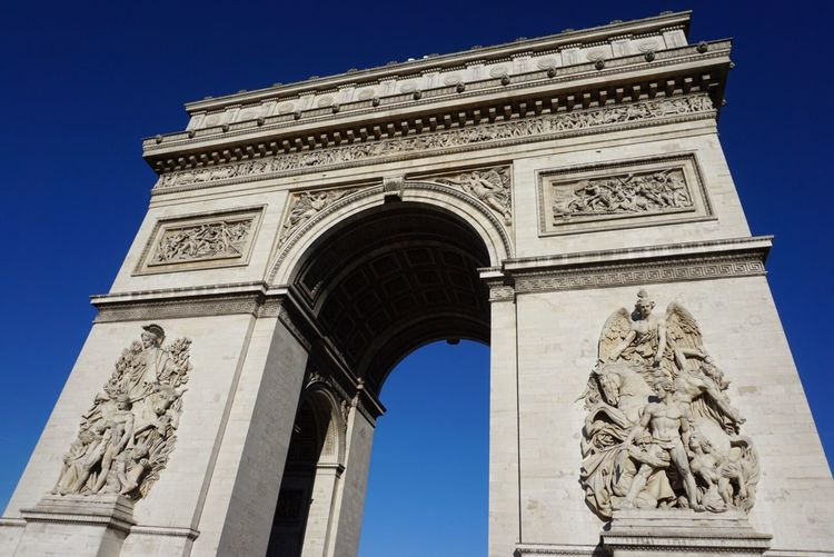 Low angle view of arc de triomphe on sunny day