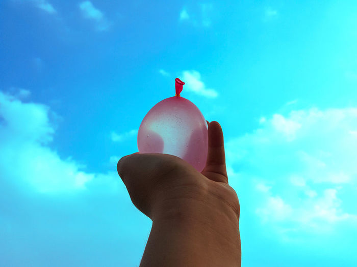 Low angle view of person hand against blue sky