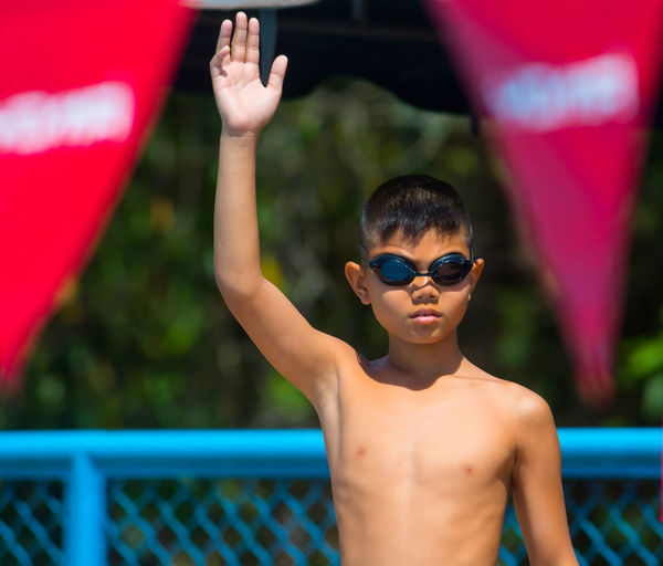 Portrait of shirtless boy with hand raised in sunny day