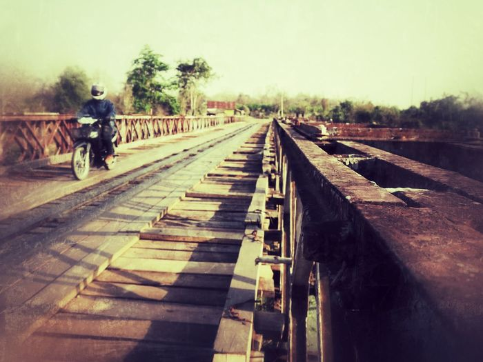 Man on railroad track against sky