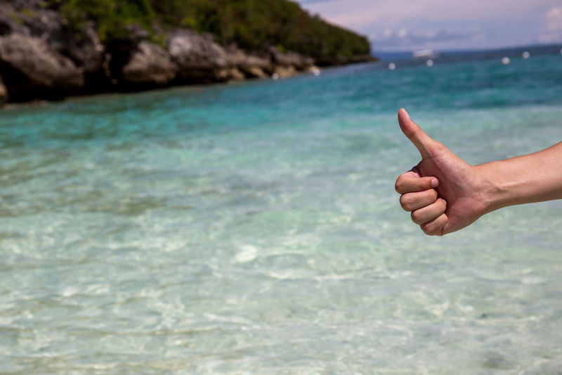 Close-up of hand showing thumbs up against sea
