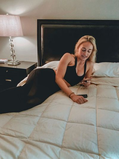 Young woman using mobile phone while relaxing on bed at home