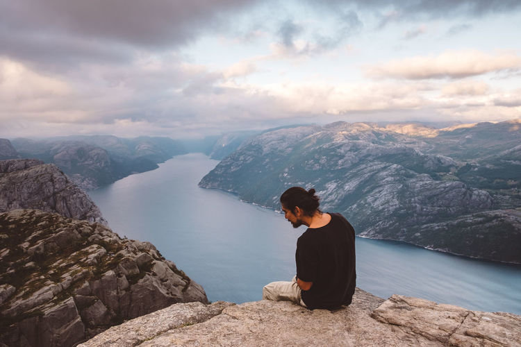 Man sitting on rock looking at mountains against sky