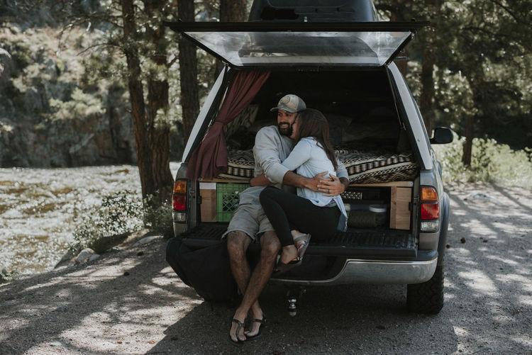 Full length of man sitting on car