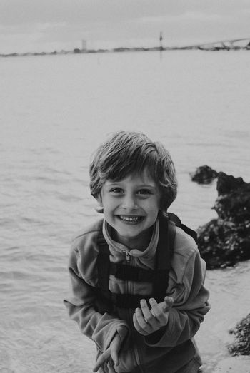 Childhood Looking At Camera Portrait Boys Outdoors One Person Happiness Real People Smiling Water Winter Leisure Activity Front View Standing Elementary Age Day Lake Nature Sky Warm Clothing This Is Masculinity