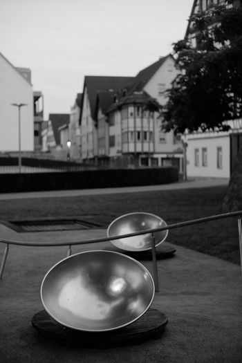 Close-up of bowl on table by buildings in city