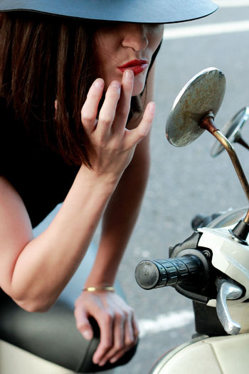 Woman touching lips while looking in side-view mirror of motor scooter
