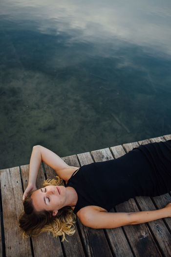 Woman lying down on pier by river against sky