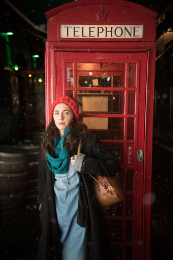 Portrait of woman standing against telephone booth