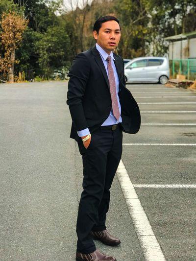 Portrait of businessman standing on road in city
