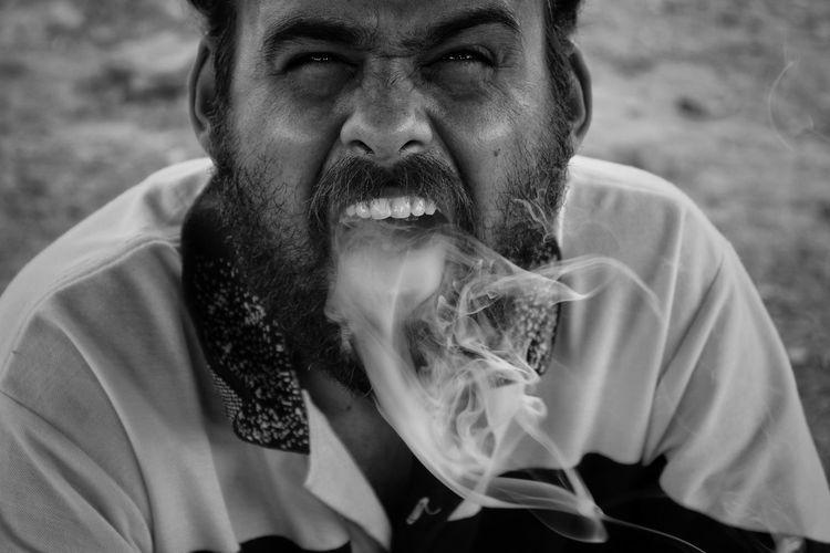 Portrait of man emitting smoke