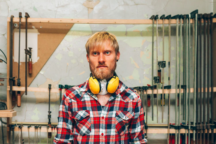 Portrait of young wood worker man inside workshop studio with tools in background
