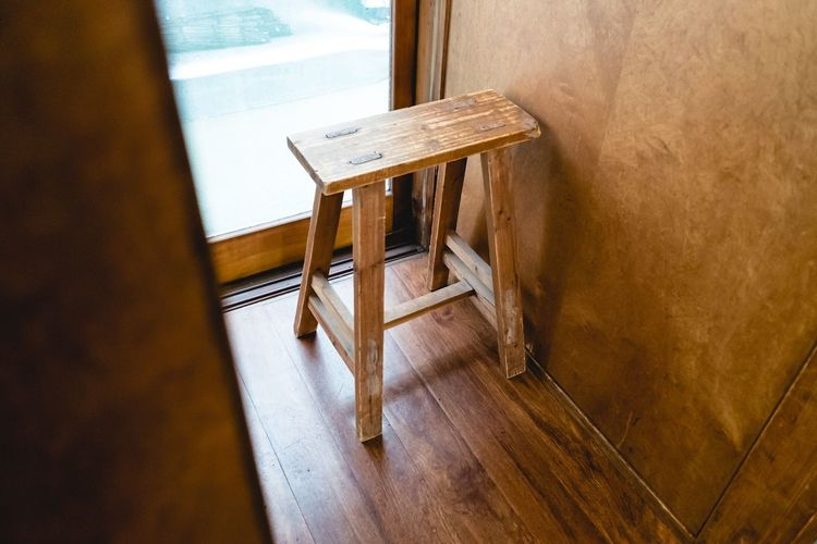 High angle view of wooden stool by window