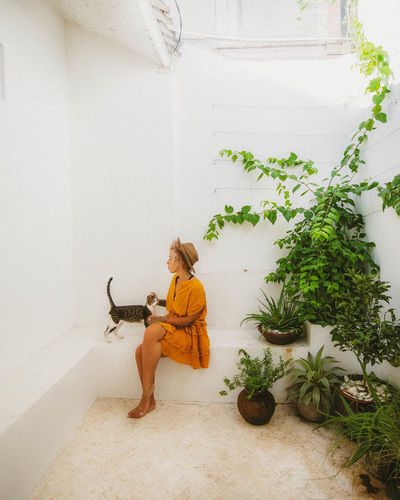 Young woman sitting by potted plant at home