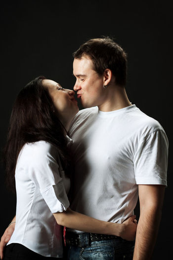 Romantic Young Couple Kissing Against Black Background