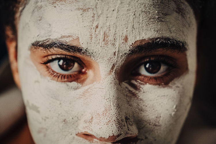 Cropped portrait of teenage girl with facial mask
