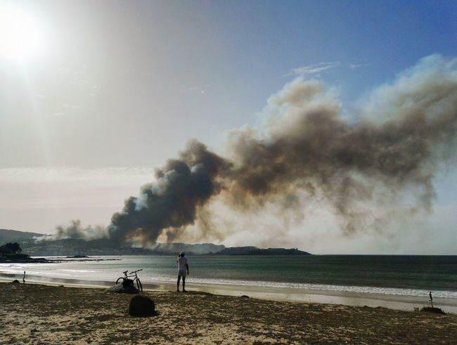 Water Spraying Heat - Temperature Firefighter Sky People Beach Adult Men Standing Real People Adults Only Sea Outdoors Day Power In Nature Only Men