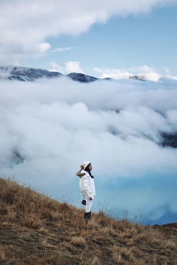 High angle view of woman looking away while standing against foggy landscape