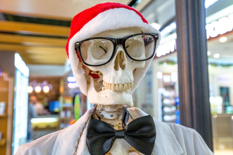 Close-up of human skeleton wearing santa hat outside shop