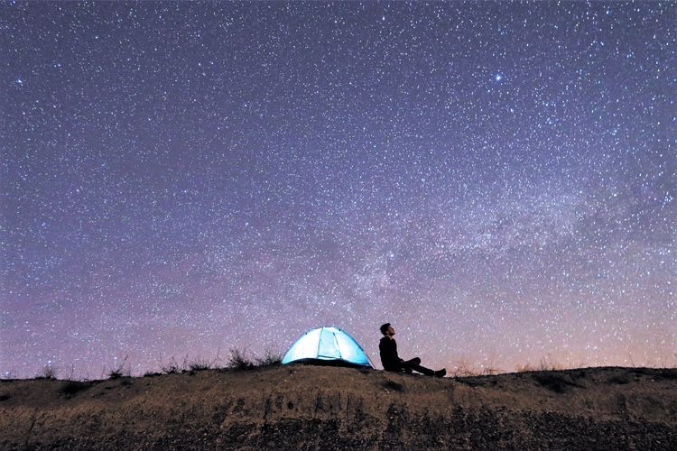 Man sitting on land against star field at night