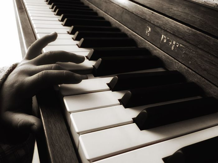 Cropped hands of child playing piano