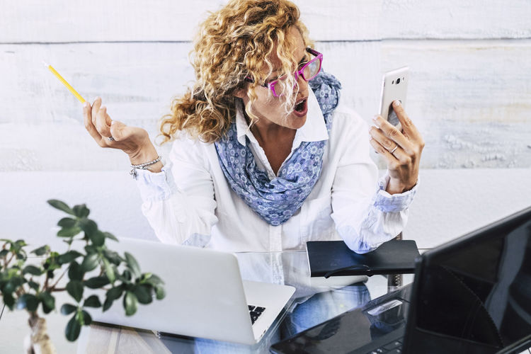 Young business woman manager shout at the phone during work call - stress and people using technology in the office at the desk - female boss shouting at mobile cellular device Wireless Technology Communication Technology One Person Mobile Phone Women Holding Adult Portable Information Device Sitting Smart Phone Females Waist Up Connection Telephone Front View Curly Hair Using Phone Hair Hairstyle Shouting Businesswoman Young Adult Office Contrast Conversation Caucasian Casual Clothing Scarf Plant Laptop Stressed Freelance Explaining  Negative Emotion Anger 40-44 Years