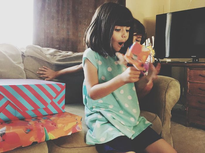 Happy birthday girl! Opening presents Sitting Sofa Real People Furniture Indoors  Lifestyles Casual Clothing Young Women Holding Child Leisure Activity People Home Interior Females Emotion Young Adult Girls Women