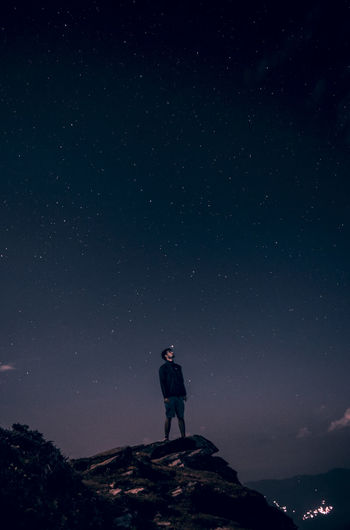 Low angle view of young man standing on cliff against star field