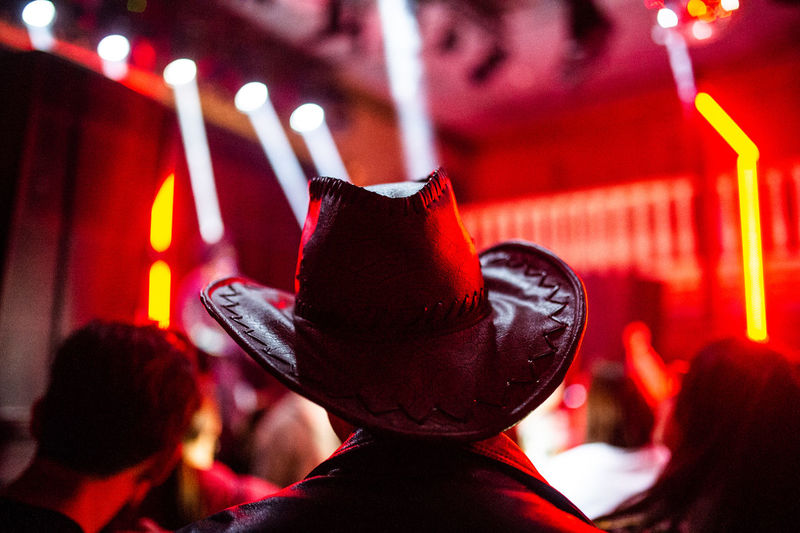Rear view of man wearing cowboy hat at nightclub