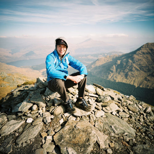 A hiker rests atop the windy peak of Ben Vane in the Scottish Highlands. Adventure Beauty In Nature Ben Vane Day Full Length Happiness Hiking Leisure Activity Looking At Camera Men Mid Adult Men Mountain Mountain Range Munro Nature One Person Outdoors Portrait Real People Scotland Scottish Highlands Sitting Smiling Sunset Young Adult