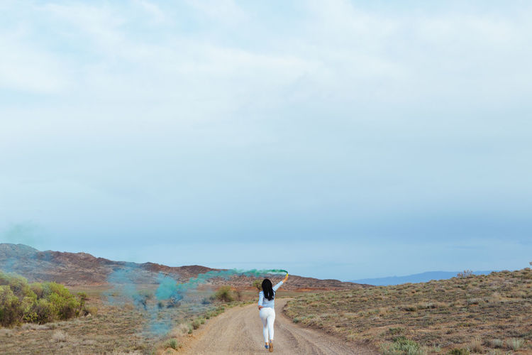 Rear view of woman holding distress flare while running on dirt road against cloudy sky
